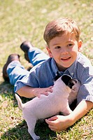 Boy lying on a lawn holding a puppy