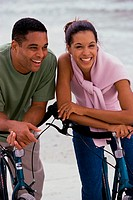 Young couple with bicycles on the beach