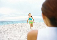 Girl running towards mother on beach