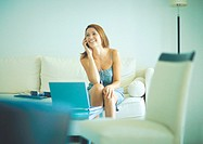 Woman using cell phone, sitting on couch