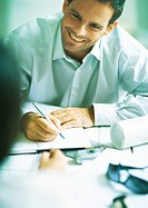Man smiling and writing in agenda, looking at second person