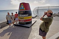 "Man taking a picture of people standing next to the ""Southernmost Point"" marker in Key West, Florida. December 2004"