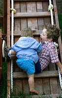 Baby and brother on ladder