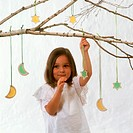 Small girl under birch branch with Christmas tree ornaments