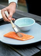 Brushing salmon fillet with oil