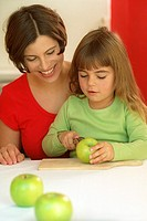 Mother and daughter cutting an apple