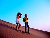 Western tourist taking pictures in the desert of the United Arab Emirates