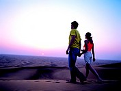 Western couple walking in the desert at sunset, Hatta, United Arab Emirates
