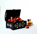 Arab traditions - dried dates in a box and a cup of tea