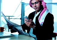 Saudi Arabian businessman reading newspaper and checking mobile phone