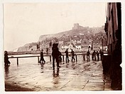 Photograph by Frank Meadow Sutcliffe (1853-1941) of Whitby Harbour, taken at Coffee House Corner on the harbour front. The man in the foreground is pr...