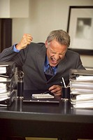 businessman behind his desk raising his fist in anger