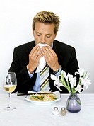 man in suit using a napkin in restaurant