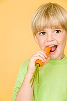 Little boy eating carrot