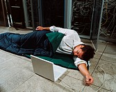 Man sleeping next to laptop