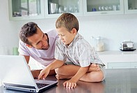 Father showing son how to use laptop