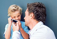 Father letting son use mobile phone