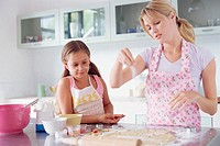 Girl helping mother make biscuits