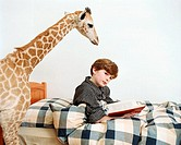 Boy reading with giraffe looking over his shoulder