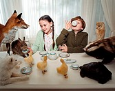 Children having a tea party with animals
