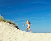 Girl walking up a sand dune