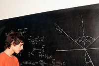 Student looking at equation on blackboard