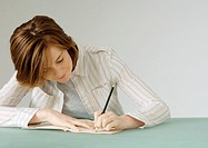 Young woman with notebook, erasing