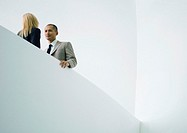 Businessman and businesswoman standing face to face, low angle view (thumbnail)