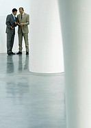 Two businessmen standing in lobby, looking at cell phone (thumbnail)