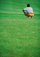 Golfer crouching on green, rear view