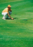 Golfer crouching on green, pointing golf club