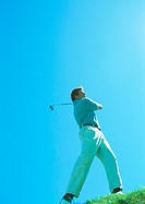 Golfer swinging, low angle view