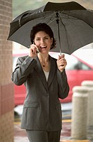 Woman holding umbrella and cell phone