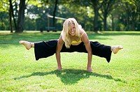 Young woman doing gymnastics in park