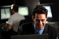A business man looking smiling at a computer screen