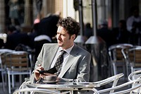 A man sitting outside a café holding a palm computer