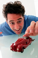 A man playing with a red toy car