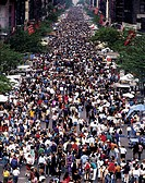 A crowd of people enjoying the Ninth Avenue Food Festival in New York City.