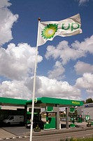 'BP' gas station flags with cloudy sky