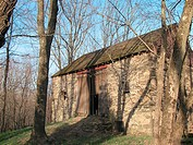 An ancient stone barn stands in the forest