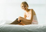 Young woman sitting on bed, putting on stockings