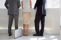 rear view of three business people standing at reception desk