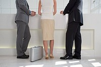 rear view of three business people waiting at reception