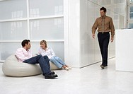 man and woman talking in office building while another man is passing by