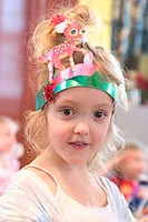 3 year old girl at a party wearing a party hat smiling straight into camera