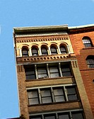 Light blue sky with close details of two older buildings in downtown New York. USA