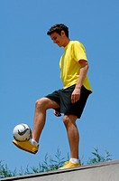Teenage boy juggling soccer ball