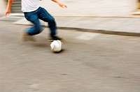 Man running with soccer ball in street