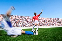 Soccer player kicking ball as defender slides in