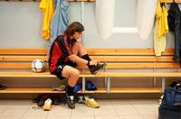 Soccer player tying boots in changing room